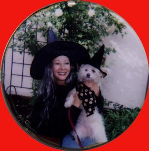 A pet owner and her dog each dressed as Halloween witches