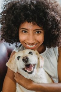 Black woman with fabulous natural hair and amazing smile has her arms wrapped around a cute smiling mixed-breed blonde dog