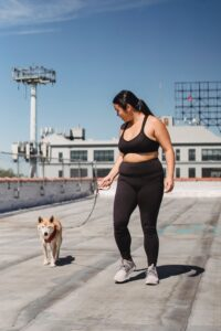 Shiba Inu walks with a young Asian woman in athletic wear