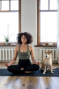 Black woman sits in a yoga or meditation pose with a shiba inu dog sitting next to her.