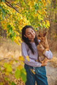 Young woman with long dark hair looks lovingly at a small dog in her arms