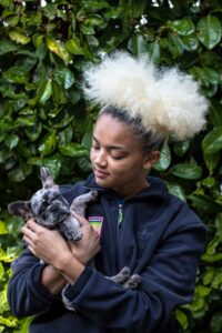 Person with amazing hair holds brindle French bulldog puppy