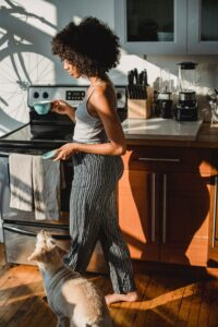 Woman in casual clothes and fabulous afro talks out of a kitchen area with a teacup in one hand, and a saucer in the other, with her mixed-breed terrier following at her feet